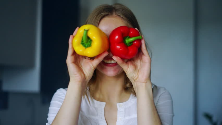 Smiling girl covering his eyes with paprika peppers. Happy girl with fresh vegetables. Close up girl fool around at camera. Healthy eating. Vegetable diet concept. Yellow and red peppers