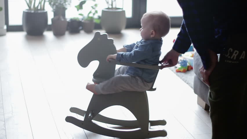 Boy toddler baby swinging on a rocking chair in the shape of a horse, slow motion | Shutterstock HD Video #1015387465