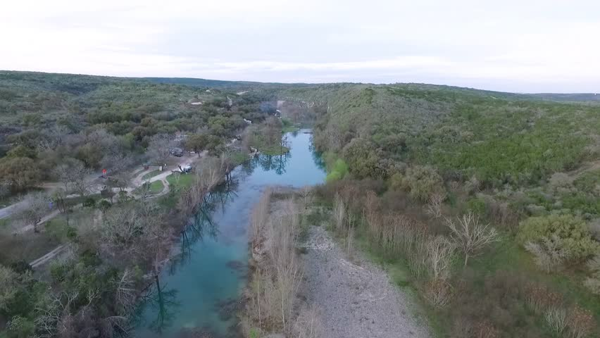Aerial footage from a drone flying over Paradise canyon river San Antoni Texas Great place for tubing.   Shutterstock HD Video #1015388335