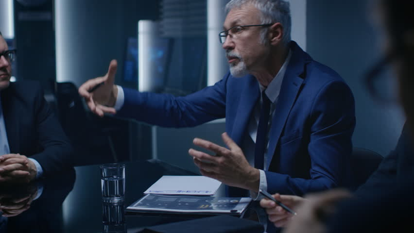 Portrait of the Corporate Businessman having Heated Debate with His Business Partners During Weekly Meeting. Serious Business People. Shot on RED EPIC-W 8K Helium Cinema Camera.
