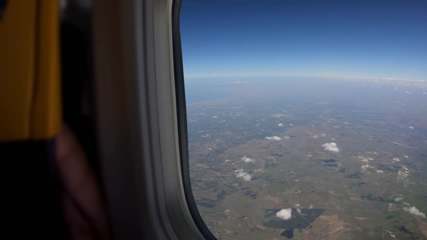 4K. Fields seen through the window of airplane with the front seat. Travel in aircraft. POV of the passenger tourist traveling on a plane that is turning-Adrian