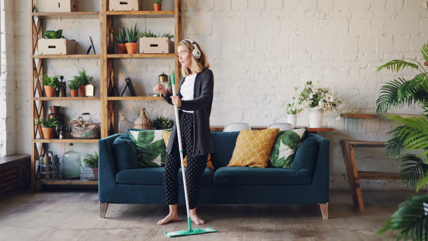 Pretty young woman is dancing and singing listening to music through headphones during housework at home, girl is dancing with mop moving around and having fun. | Shutterstock HD Video #1015401496