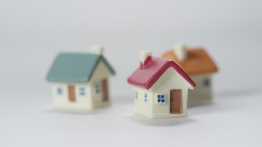 Investment Properties Money and Home Ownership Model toy house on white background