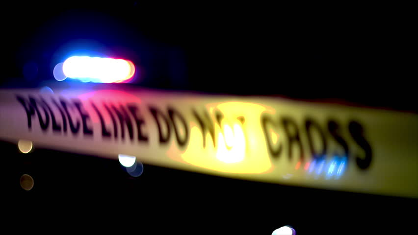 Crime scene at night with flashing police lights and crime scene tape. Authorized personnel only at a forensic investigation. Police and crime concept.