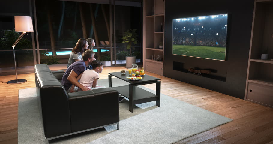 A family is watching a soccer moment on the TV and celebrating a goal, sitting on the couch in the living room. The living room is made in 3D. #1015440919