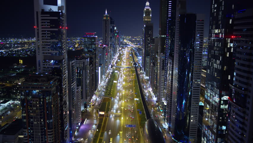 Aerial night illuminated city view Sheikh Zayed road skyline skyscrapers commercial condominiums suburbs vehicle transport highway metro UAE Dubai RED WEAPON #1015444645