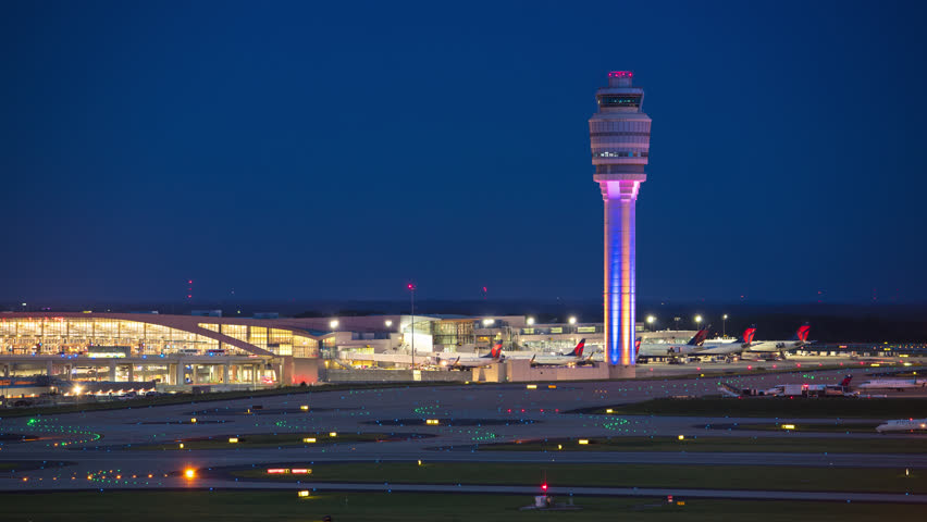ATLANTA, GA - 2018: ATL Hartsfield Jackson International Airport Nightscape Timelapse featuring the Air Traffic Control Tower and Terminal Building Exterior with Streaking Lights from Airplanes