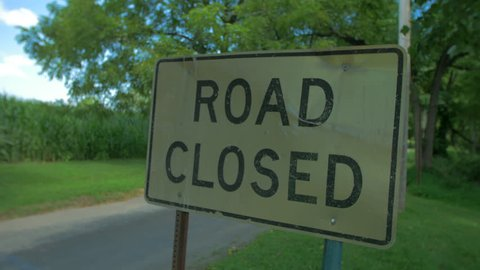 Road Closed sign slow move in