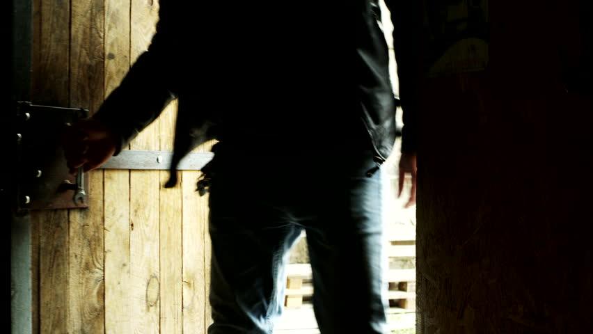 Man entering door. Biker come in garage. Close up of entering door in dark. Man come home. Hipster enter door. Guy come inside