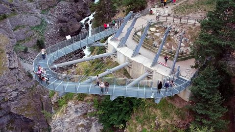 """Prè Saint Didier, Aosta / Italy - 08/18/2018 : Aeriali view of the footbridge suspended over the """"Orrido"""" of Pre Saint Didier, the alpine stream of pure water flowing in a gorge"""