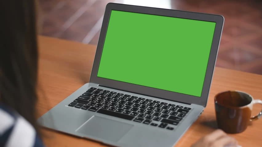 Over the shoulder shot of a business woman working in office interior on pc on desk, looking at green screen. Office person using laptop computer with laptop green screen, sitting at wooden table | Shutterstock HD Video #1015488580
