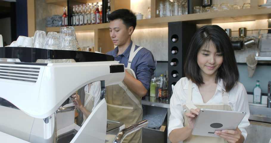 Young asian barista using tablet computer during a break on the work in the coffee shop. | Shutterstock HD Video #1015492405