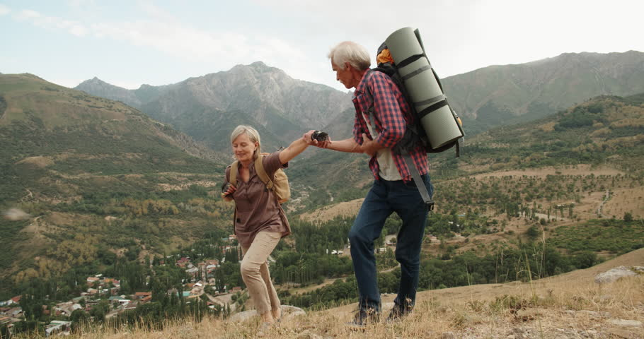 Mature caucasian senior on a hiking adventure taking wife's hand helping her climb up a mountain. tourism concept 4k | Shutterstock HD Video #1015494784