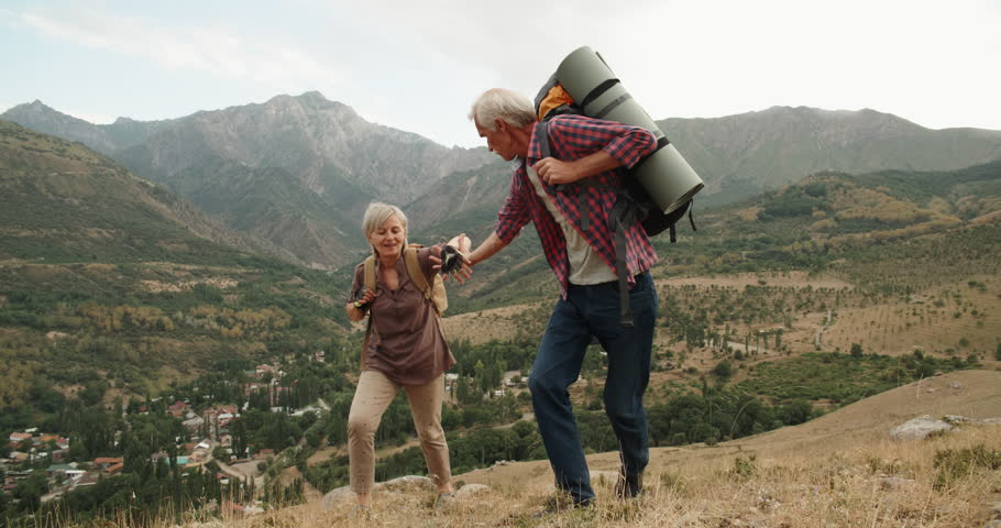 Mature caucasian senior on a hiking adventure taking wife's hand helping her climb up a mountain. tourism concept 4k