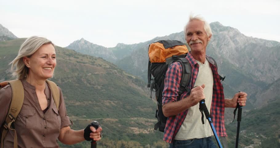 Positive mature caucasian couple trekking in mountains with backpacks, enjoying their adventure 4k | Shutterstock HD Video #1015494796