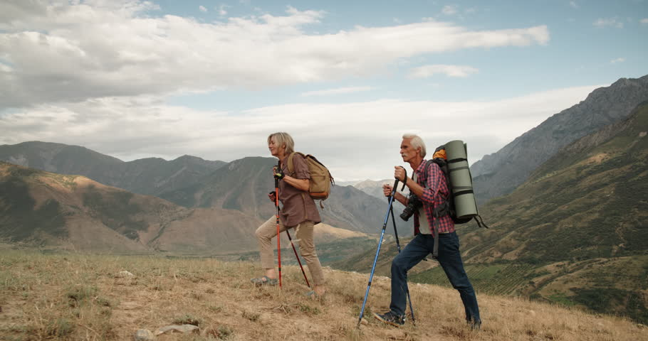 Active senior caucasian couple hiking in mountains with backpacks, enjoying their adventure 4k | Shutterstock HD Video #1015494799