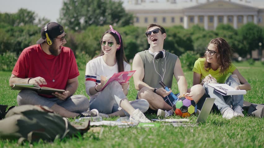 Students sitting on grass in the park and talking. Group of young people spending time together outdoors and smiling.