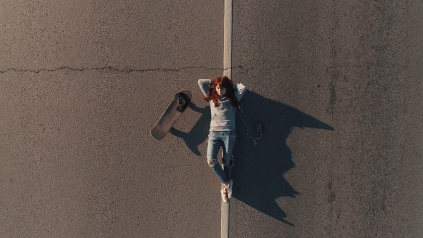 Aerial. A teenager with a skateboard and lies on the roadway and listens to music on headphones. young girl hippy. View from above | Shutterstock HD Video #1015514749