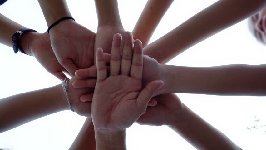 Successful team: many hands holding together on sky background  #1015527244