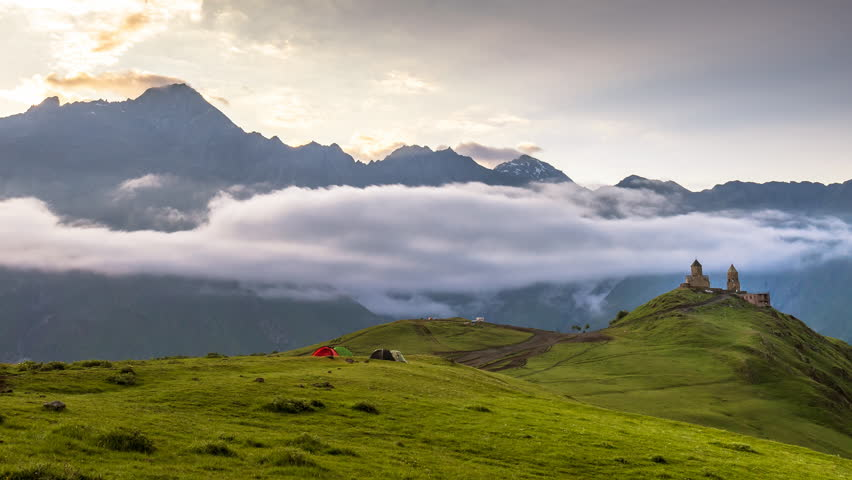 Ancient Gergeti Trinity church near mount Kazbek, Georgia. People photograph the ancient church. | Shutterstock HD Video #1015527247