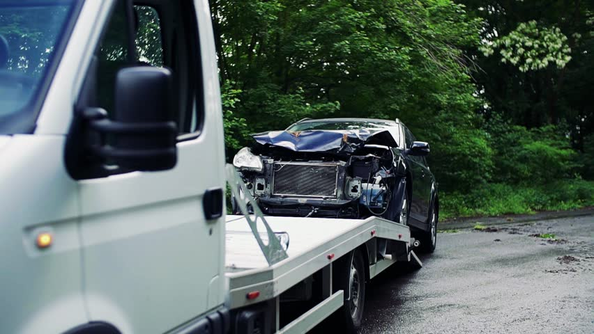 A crashed car being put on a tow truck after an accident.