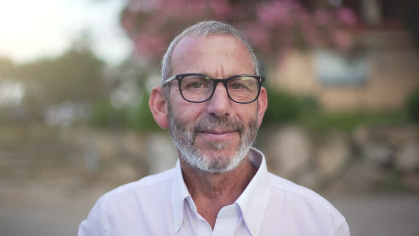 Closeup portrait of mature man, businessman, with beard, black glasses and white shirt looking at camera and smiling in slow motion. | Shutterstock HD Video #1015558870