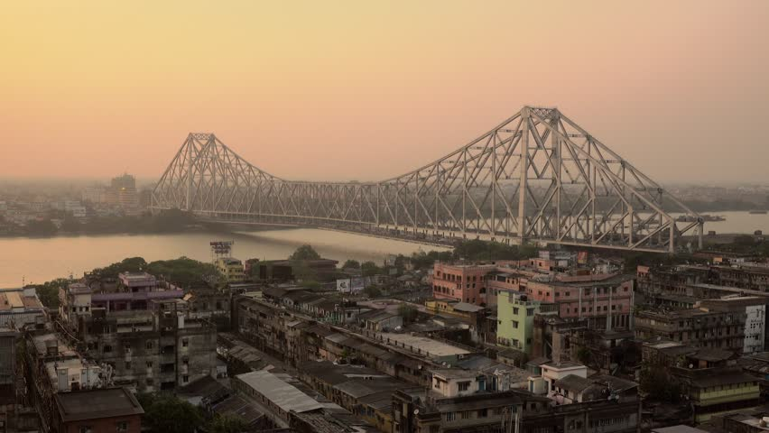 Beautiful sunset view of Kolkata city with a Howrah bridge on the Ganga river, West Bengal, India.
