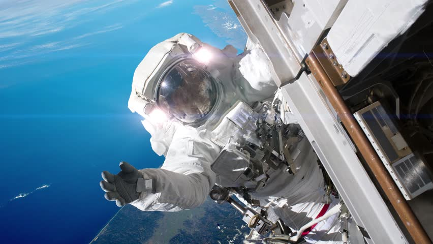 Astronaut working on a spaceship. Elements of image furnished by NASA.