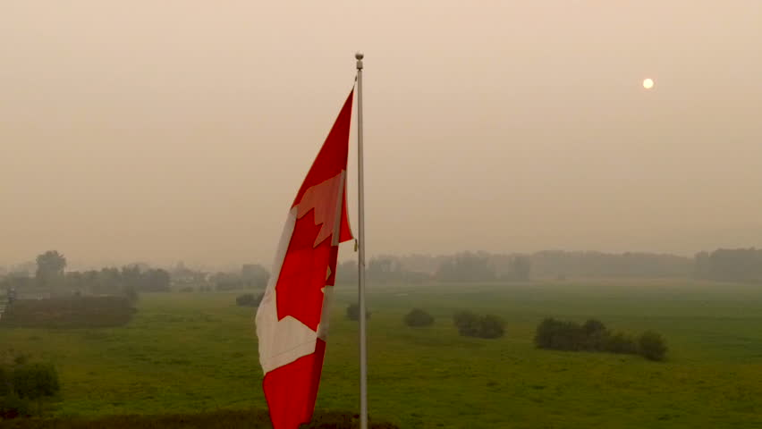 Beautiful smoky sunset cause by near by forest fires in BC Canada in background of slow motion waving canadian flag | Shutterstock HD Video #1015580704