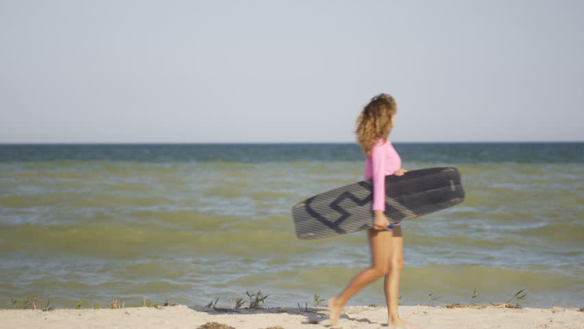 Girl with kiteboard is walking along the beach tropical beach at sunset . Girl holding board in hand | Shutterstock HD Video #1015581766
