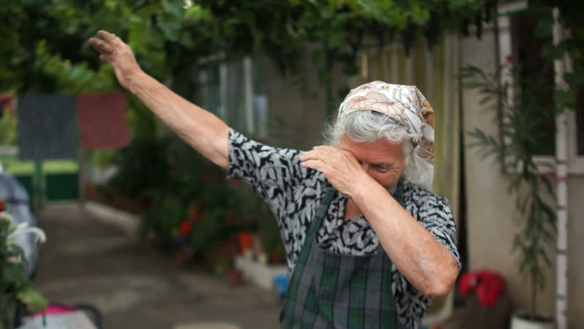Grandmother shows a fashionable youth movement dab. Modern dance, sense of humor   Shutterstock HD Video #1015582561