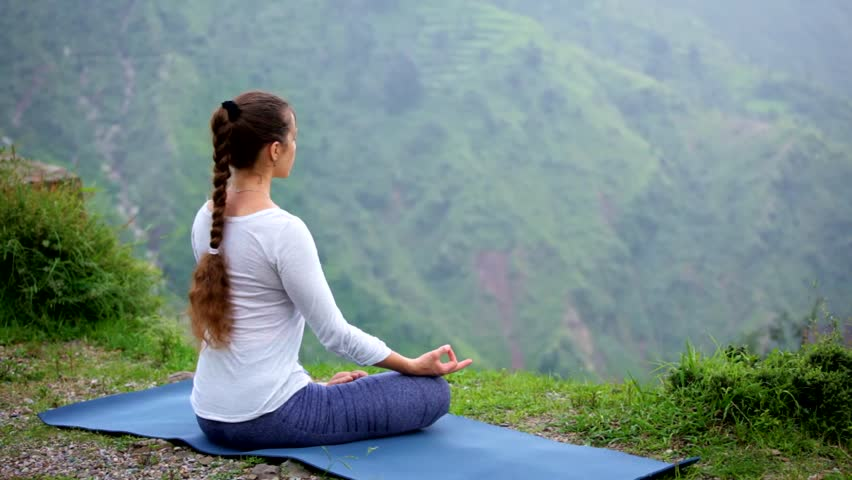 Woman doing yoga - meditating in Padmasana (Lotus Pose) outdoors in mountains on sunset   Shutterstock HD Video #1015584124