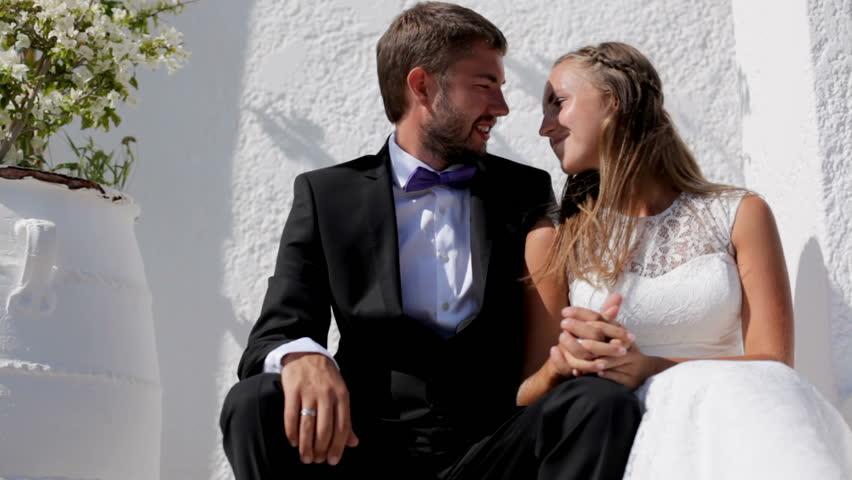 Happy newlyweds sitting near their hotel on their wedding day. | Shutterstock HD Video #1015594762