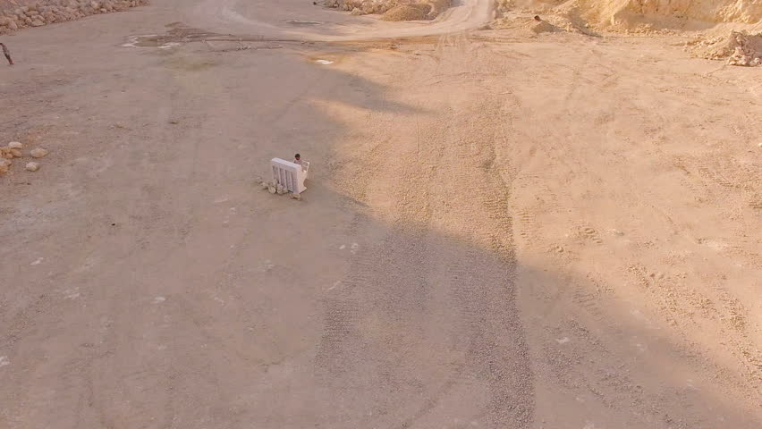 Drone flies over a deep foundation pit in which a man plays the piano. Aerial view   Shutterstock HD Video #1015606204