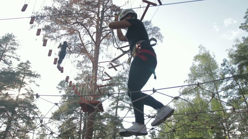 Young beautiful brunette overcomes obstacles in the rope town. A girl with a white helmet on her head and protective gear is on the track   Shutterstock HD Video #1015610650