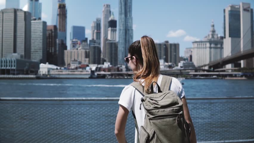 Back view of young happy tourist girl with backpack and arms wide open with joy at famous Manhattan skyline in New York