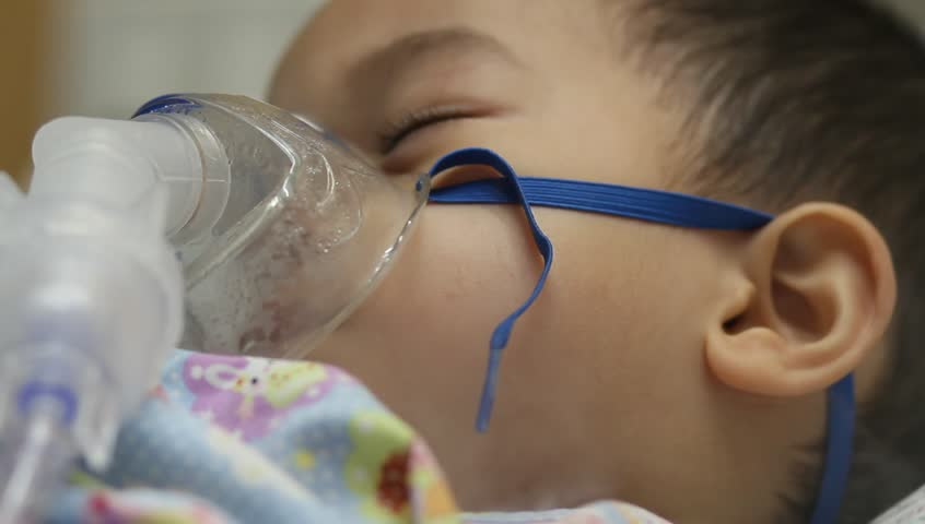 2 years old Asian toddler boy has asthma or pneumonia disease and need nebulizations,Sick boy rest on patient bed and has inhalation therapy by the mask of inhaler.Sick or cancer child awareness. Royalty-Free Stock Footage #1015622797