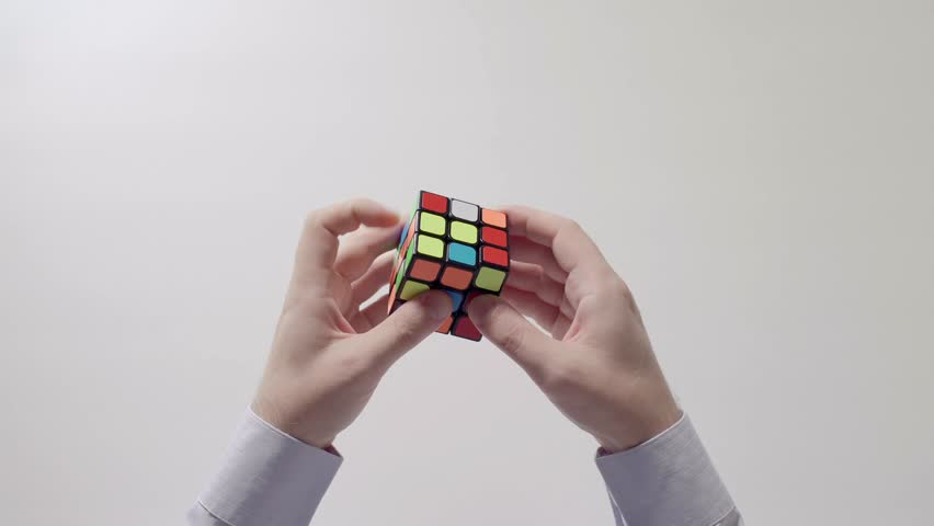 TAIPEI, TAIWAN - AUGUST 21, 2018: Businessman's hands solving rubik's cube puzzle. Puzzle cube, puzzle game, best-selling toys. Man's hands in a shirt closeup. Rubik's cube is solved.Part 02. Speed up