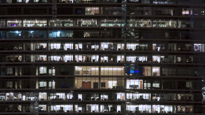 Timelapse at night of a modern office building with glass windows and lights going on and off #1015654081