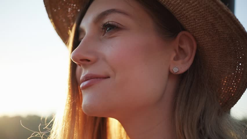 Close up of woman's face with hat smile feel happy outside at sunrise sunset beautiful girl lifestyle nature people summer eyes portrait background beach outdoor relax sunlight portrait slow motion Royalty-Free Stock Footage #1015656160