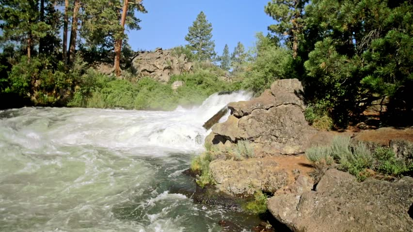 Panning shot of water rushing down from the crest of a small waterfall on a gorgeous river in Bend, Oregon