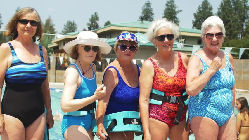 Five adorable old ladies wearing festive bathing suits and sunglasses stand by the pool, and flex their muscles at the camera | Shutterstock HD Video #1015666162