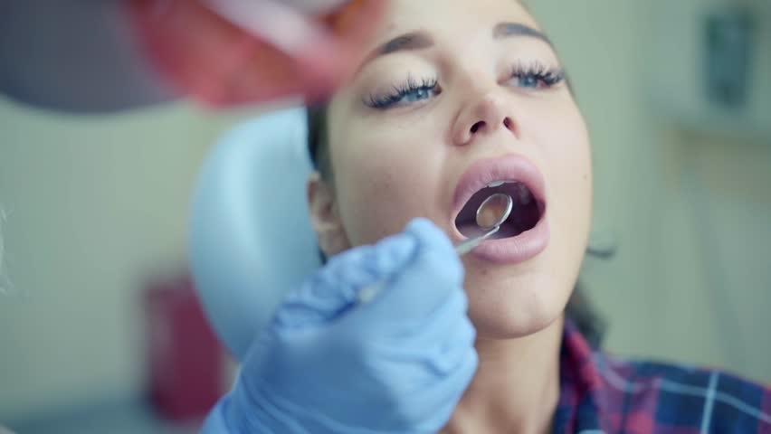 Dentist examining patient young woman teeth using mirror in clinic | Shutterstock HD Video #1015666567