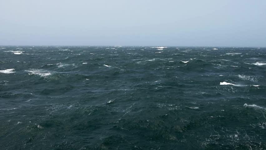 Cargo ship rolling in stormy sea. Huge waves of summer monsoon in Indian Ocean