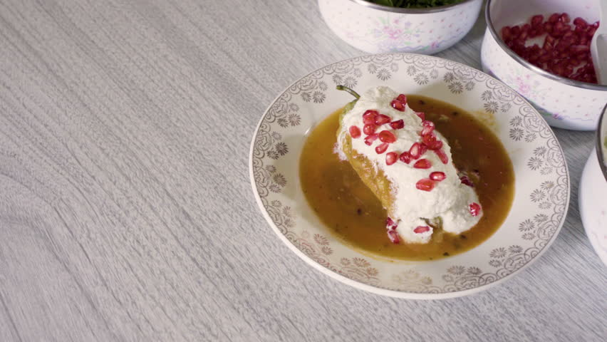 Chiles en nogada, traditional mexican dish from Puebla, Mexico. It consists of poblano chilis filled with picadillo topped with a walnut-based cream sauce, pomegranate and chopped parsley.  | Shutterstock HD Video #1015697020