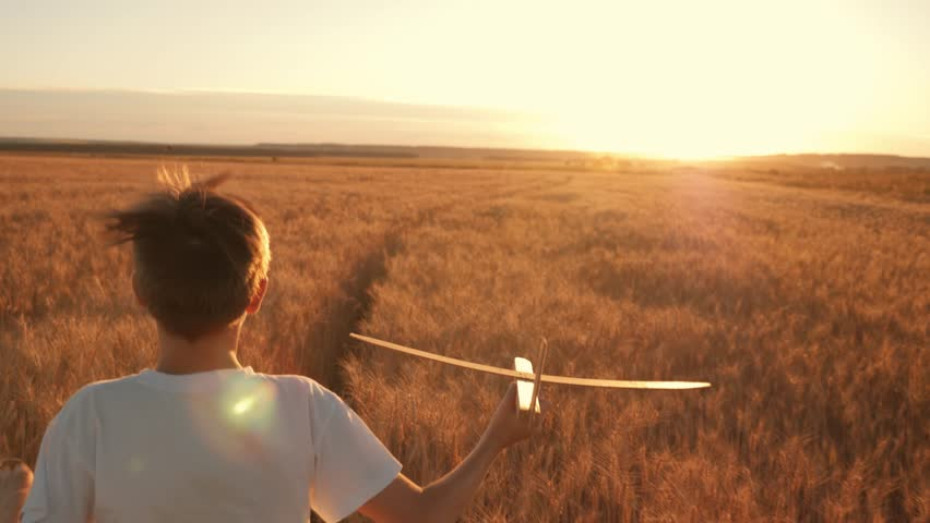 Happy child runs with a toy airplane on a sunset background over a field. The concept of a happy family. Childhood dreams | Shutterstock HD Video #1015709296