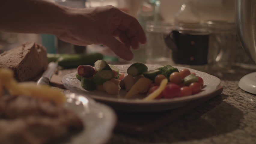 Hands grabbing vegetables and putting them on a plate with cooked chicken in 4k.   Shutterstock HD Video #1015719502