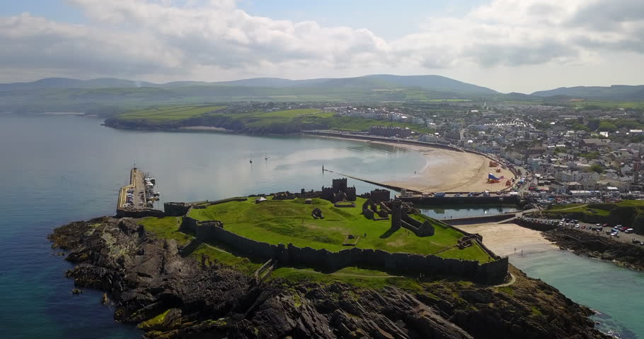 Drone flying over Peel Castle on Isle of Man, landmark building in Peel on the Isle of Man, originally constructed by Vikings. Aerial view of charming sea town and old monument seen from the sky
