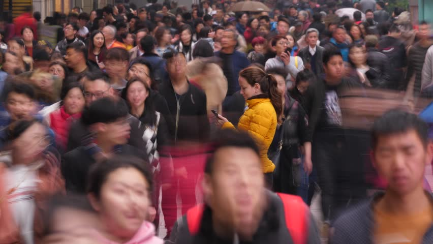 SHANGHAI - MARCH 18, 2018: Unidentified Asian people fuss around, woman (model released) stay still, stare to smartphone. Time lapse shot of busy and crowded Nanjing Road