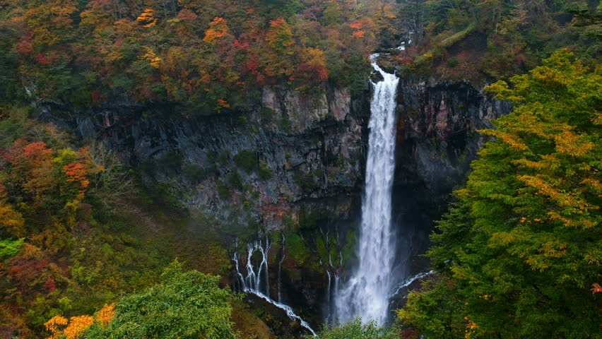 Kegon Waterfall from lake Chuzenji in Nikko national park , Kegon waterfall against white isolated sky in landscape and autumn trees in front, beautiful waterfall in autumn season in Tochigi ,Japan. | Shutterstock HD Video #1015742356